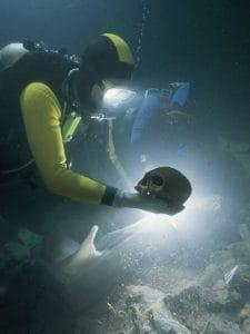 diver holds ancient native american skull