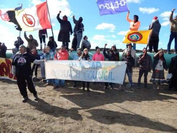 Youth Council holding their banner in front of the pipeline